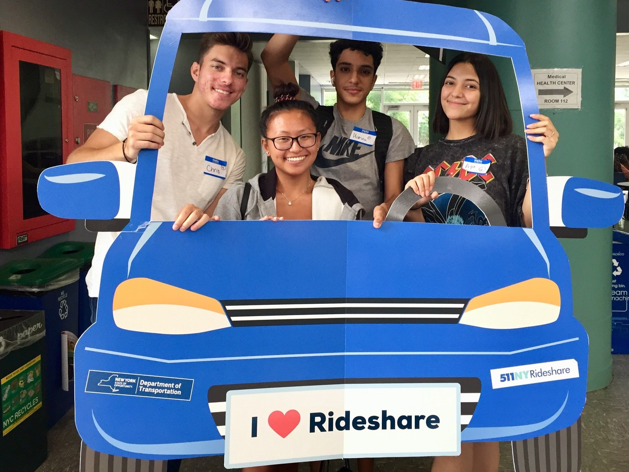 Group of students in a cardboard cutout of a car